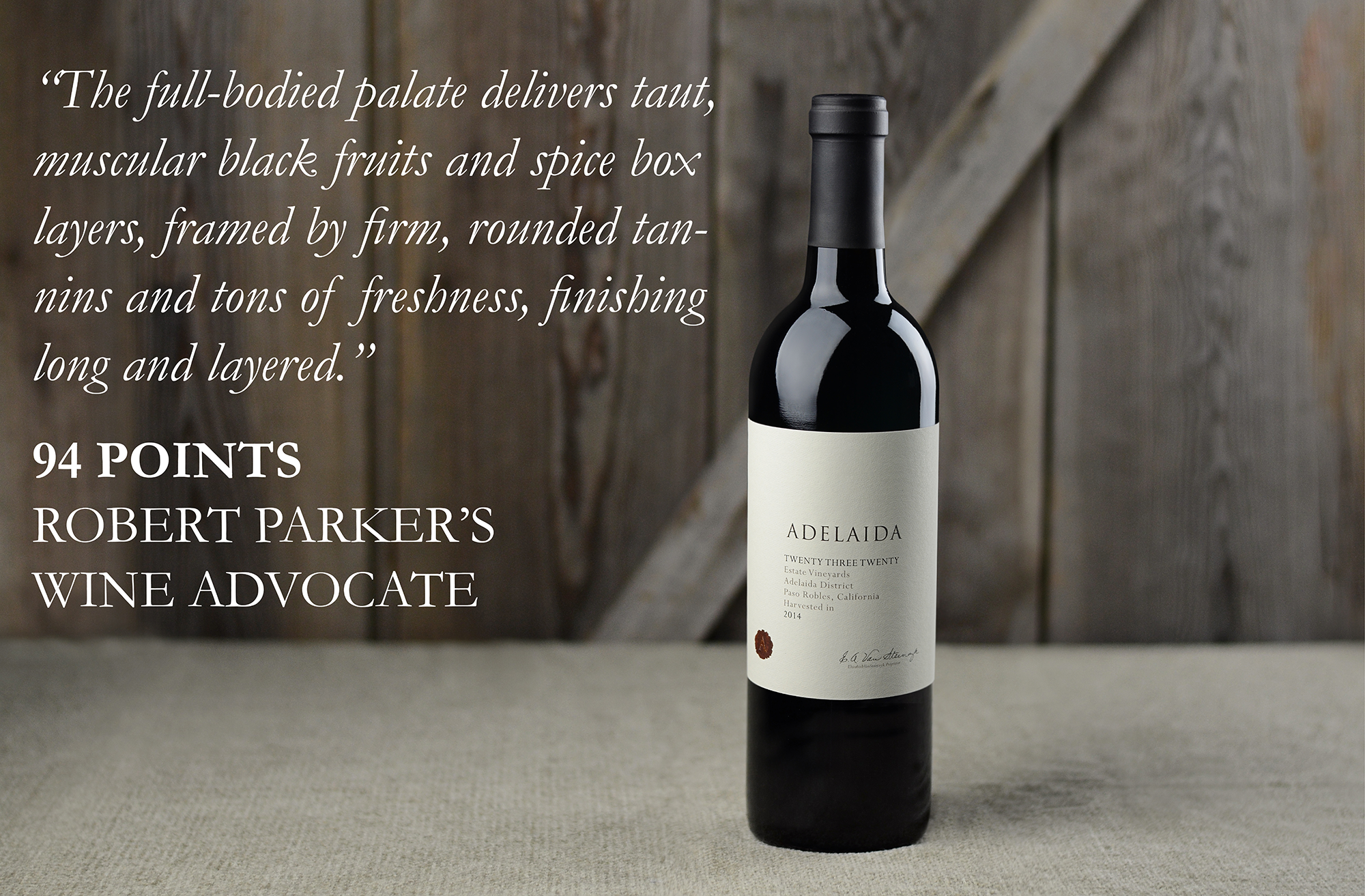 "Bottle of Twenty Three Twenty on a table with a wood background. Text says: ""The full-bodied palate delivers taut, muscular black fruits and spice box layers, framed by firm, rounded tannins and tons of freshness, finishing long and layered. 94 points Robert Parker's Wine Advocate"