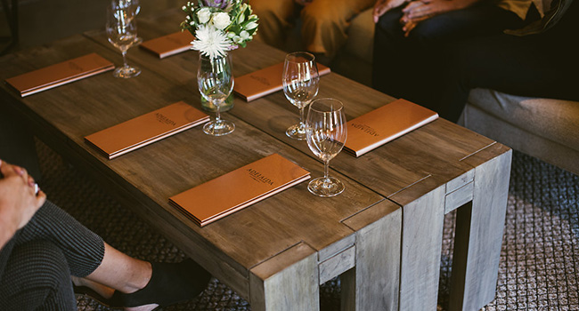 Tasting menus and wine glasses on top of a table