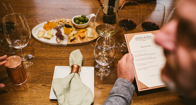 A man reading a tasting menu at a table with a cheese board and a flight of wine in front of him