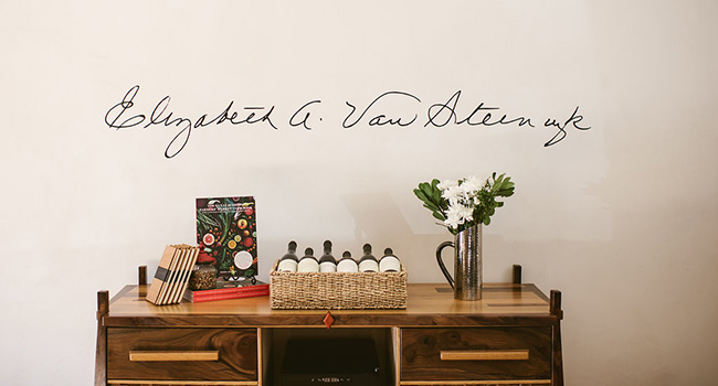 A credenza holding books, wine glasses, wine bottles and flowers in front of a wall with a signature on it