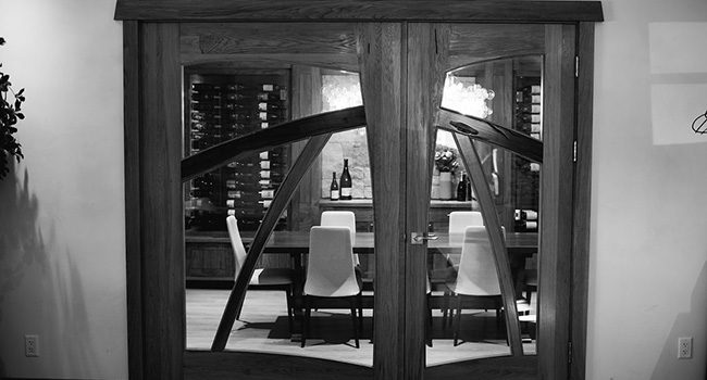 A black and white photo of a door looking into glass cases of wine
