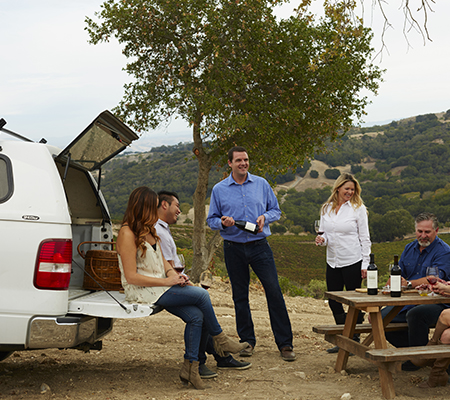 People gathered around the back of a truck and an outdoor table with wine and a picnic